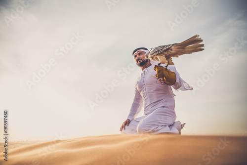 Foto  Arabic man in the desert with his hawk