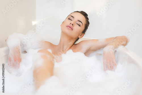 Fotografija attractive young woman taking bath with foam at home