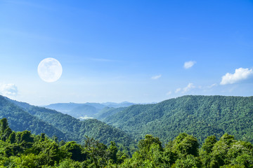 Big green mountain with big moon and blue cloud sky background