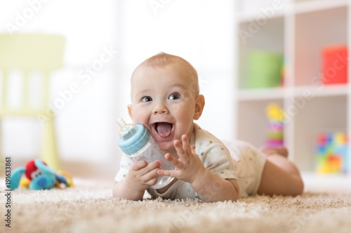 Fototapeta Cute baby boy drinking from bottle. Smiling child is 7 months old. obraz