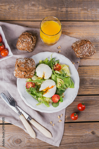 Staande foto Zuivelproducten Poached egg with green salad, tomatoes, wholemeal bread and orange juice