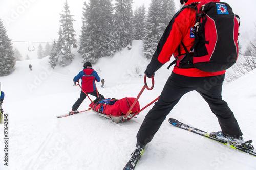 Zwei Retter der Bergwacht mit einem Rettungsschlitten - Akja