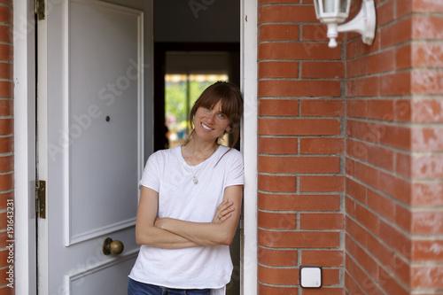 Valokuva  mujer joven en la entrada de su casa