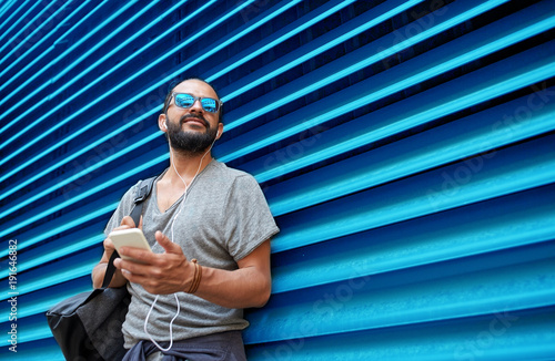 Photo sur Aluminium Magasin de musique man with earphones and smartphone over wall