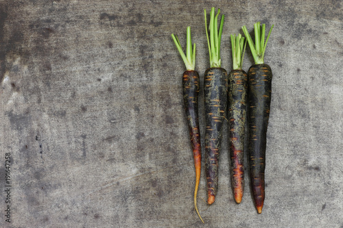 black carrots on a grungy metal background