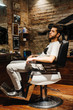 Man is sitting in a barber. Portrait of handsome hairdresser in barbershop. Stylist doing correction hairstyle at beauty salon only for real man.