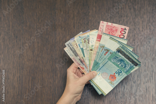 Female hand with money of south-east Asia Fototapeta