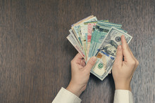 Female Hand Holding American Hundred Dollar Bills Over Asia Money.  World Markets And Trade. Choosing American Dollar As Dominant World Currency