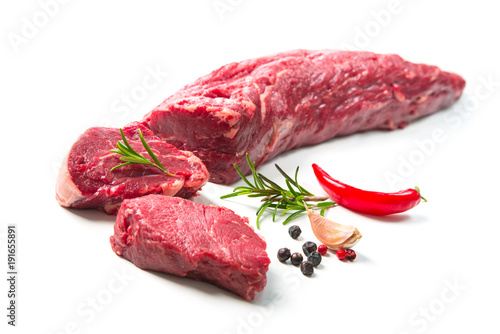 Whole piece of tenderloin with steaks and spices ready to cook isolated on white background