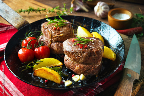 Juicy medium beef fillet steaks mignon in pan on table Canvas Print