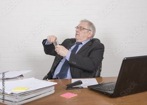 Garden Poster Mature man at work, drinking from a flask at a desk