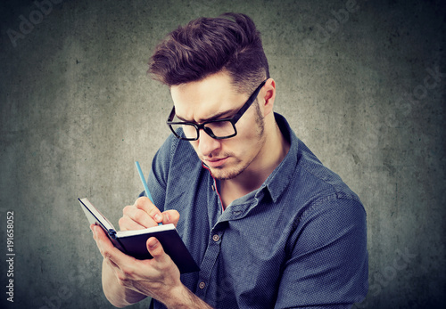 Serious man taking notes with concentration Wallpaper Mural