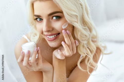 Fotografie, Obraz  Beauty Face Care. Woman Applying Cream On Skin.