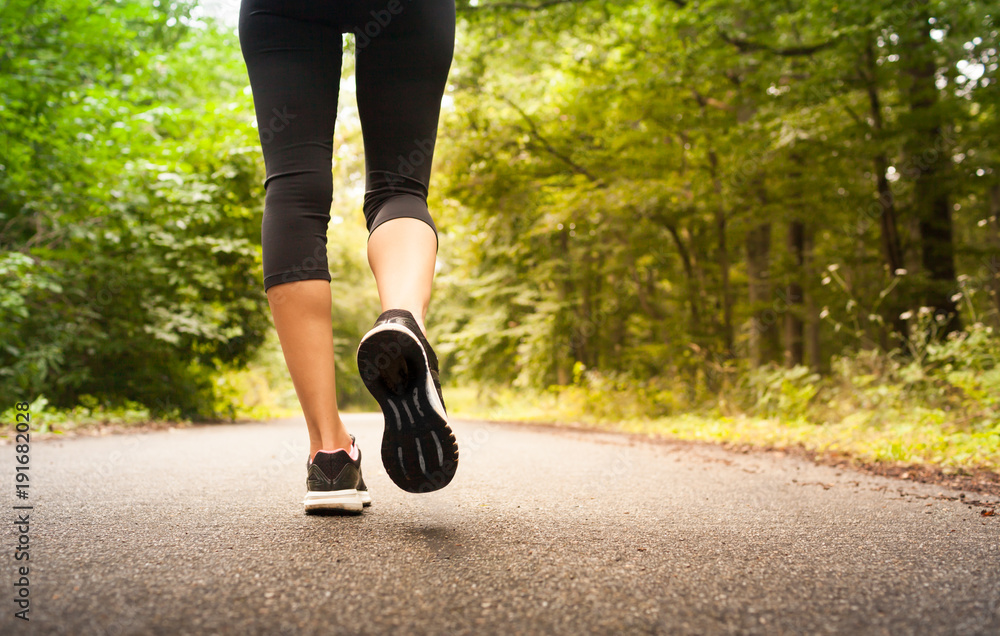 Fototapeta Woman taking a walking running on a country road.  People fitness nature concept.
