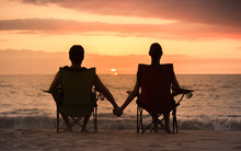Couple Relaxing On The Beach Watching The Sunset Holding Hands.