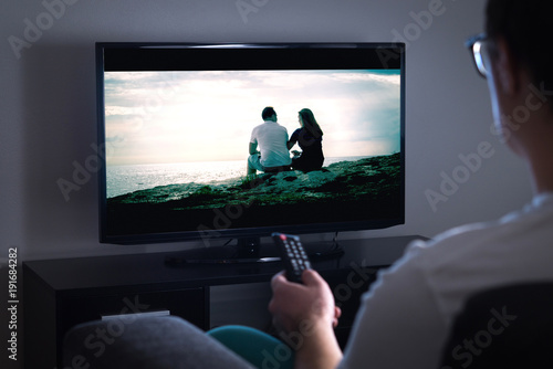 Cuadros en Lienzo Man watching tv or streaming movie or series with smart tv at home