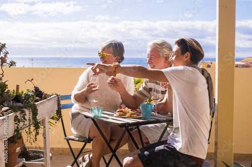 Fotografie, Obraz  couple of grandfathers with young boy teen stay together in the rooftop with ocean view in vacation