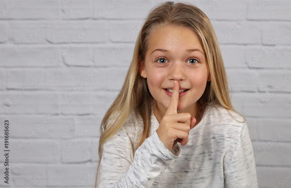 Fototapeta Portrait of happy smiling 10 years old kid girl showing silence gesture