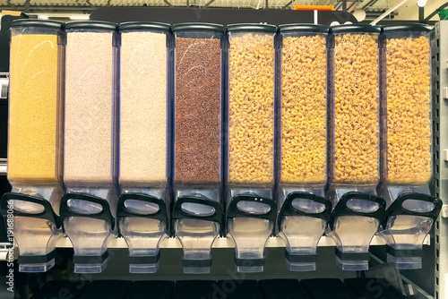 Fotografie, Obraz  millet, rice, buckwheat, pasta in the containers dispensers