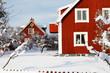 Röda bostadshus av trä omgivna av snö