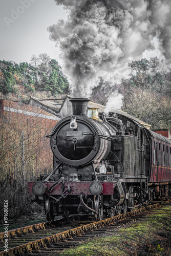 Obraz pociąg  a-upright-vertical-view-of-a-steam-train-locomotive-in-motion-facing-forward-and-smoking