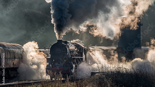 Cuadros en Lienzo  Steam train locomotive approaching a station passing through a goods yard lettin
