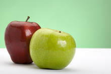 Two Apples, One Red, One Green, On A White Surface With Green Background