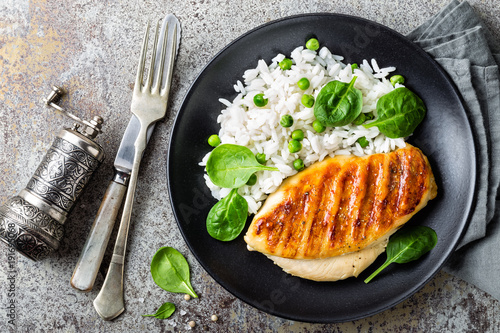 Fotografie, Obraz  Chicken breast or fillet, poultry meat grilled and boiled white rice with green peas and fresh spinach leaves