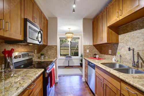 Small galley kitchen design with black kitchen appliances Fototapeta
