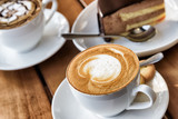 Cup of hot Cappuccino coffee on wooden table at cafe
