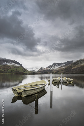 Wall Murals Pale violet Beautiful Winter landscape image of Llyn Nantlle in Snowdonia National Park with snow capped mountains in background