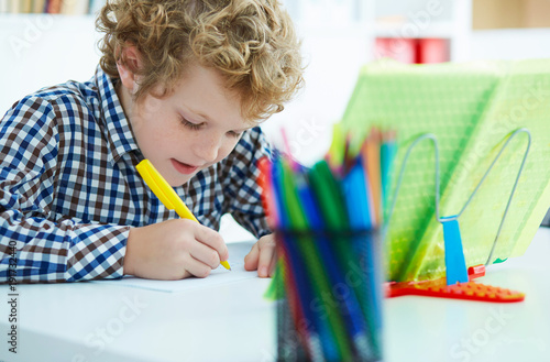Fotografía  Portrait of pupil in school class taking notes during writing lesson