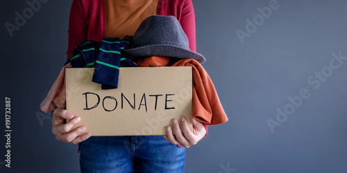 Fotografie, Obraz  Donation Concept. Woman holding a Donate Box with full of Clothes