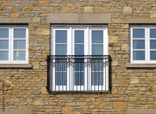 Contemporary Juliet Balcony and three windows in a stone wall
