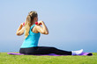 Young woman sitting on grass with dumbbells in hands on the background of the sea. Fitness girl doing exercises with weights on the beach under the morning sun. The concept of health and weight loss.
