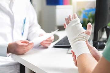 Injured patient showing doctor broken wrist and arm with bandage in hospital office or emergency room. Sprain, stress fracture or repetitive strain injury in hand. Nurse helping customer. First aid.