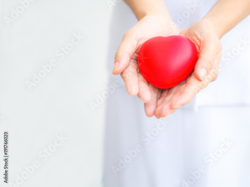 Fotografía  Red heart held by female nurse's hand, representing effort to deliver high quality service mind to patient