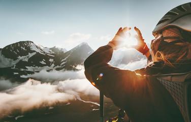 Žena rukom u obliku simbola srca oblikuje koncept načina života i osjećaja putovanja s planinama zalaska sunca na pozadini.