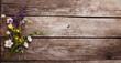 Leinwandbild Motiv Wild flowers on old grunge wooden background (chamomile lupine dandelions thyme mint bells rape)