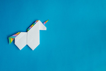 Handmade white trendy geometrical polygonal paper origami unicorn on blue background. Empty space. Horizontal poster, postcard, banner template.