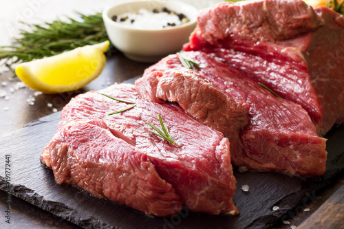 Staande foto Vlees Fresh meat. Cheese steak beef on a slate cutting board, lemon, spices and fresh rosemary on a stone table.