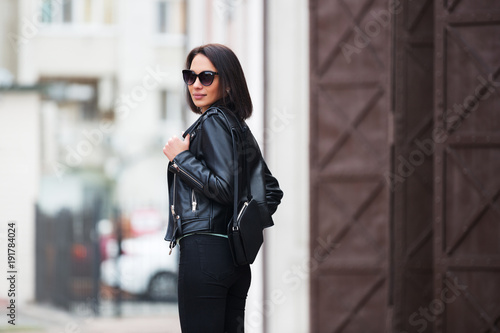 Fotografía Young fashion woman in black leather jacket walking in city street