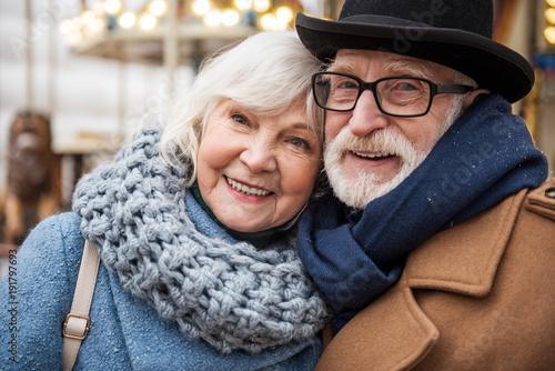 Fotografie, Obraz  Portrait of joyful senior married couple hugging while relaxing outdoor