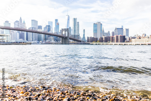 Staande foto Abu Dhabi Rocky pebble beach shore water in east river with view of NYC New York City cityscape skyline and bridge, nobody in Brooklyn
