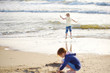 Two little sisters having fun on a sandy beach on warm and sunny summer day. Kids playing by the ocean.