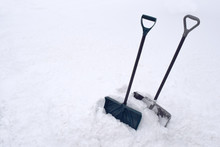 Snow Shovels In Snow Pile During Cold Winter White Snowstorm