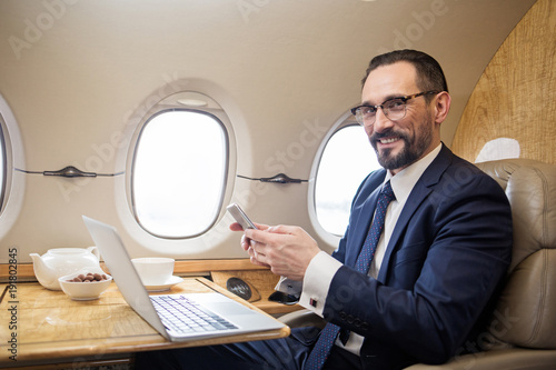 Portrait of contented diplomat sitting at tray table in airplane and holding cel Canvas Print