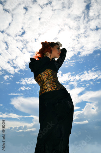 Fotografía  silhouette of a slender redheaded woman in a black dress and corset on a backgro