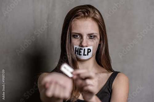 Cuadros en Lienzo Teen girl  cuts veins on a hand with a mouth taped with the inscription help