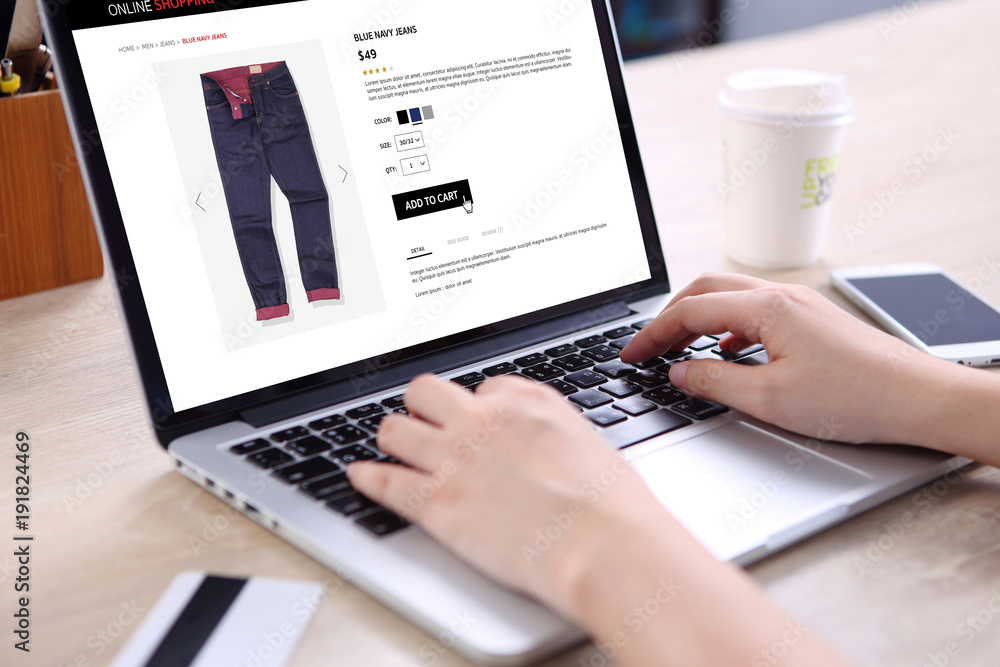 Fototapeta People buying blue navy jeans on ecommerce website with smart phone, credit card and coffee on wooden desk